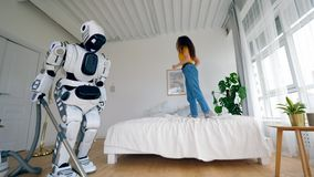 Young woman jumps on bed while a robot cleans floor. stock video footage
