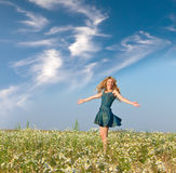 Young woman jumps in the field  of camomiles Stock Photography