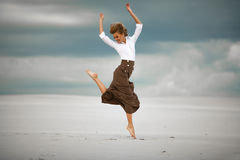 Young woman jumps on sand in desert and joyful laughs. Royalty Free Stock Images