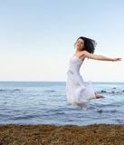 The young woman jumps on seacoast Royalty Free Stock Image