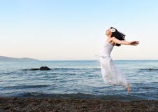 The young woman jumps on seacoast Royalty Free Stock Photography