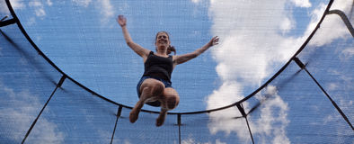 Young woman jumps on a trampolin Stock Photo