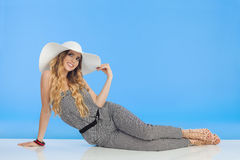 Young Woman In Jumpsuit And White Sun Hat Is Sitting On Floor And Looking Up Stock Images