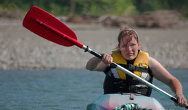 Young Woman in Kayak. This young woman is paddling in action in a kayak on the river with a red paddle in mid air and dealing with exhaustion Stock Image