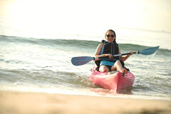 Young woman in kayak on beach during summer Stock Photography