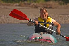Young Woman Kayaking. This young adult Caucasian woman is kayaking and is getting worn out and fatigued Royalty Free Stock Photo