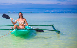 Young woman kayaking alone in the clear blue sea Stock Photo