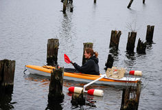 Young Woman Kayaks In Pilings Stock Photo