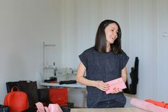 Young woman keeeping pink leather wallet at home atelier. Young craftswoman keeping pink leather wallet at home atelier. Concept of home handicraft business and Stock Photo