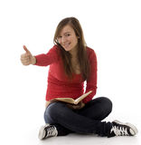 Young woman keeping book and thumb up Stock Photo