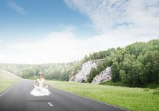 Young woman keeping mind conscious. Young woman keeping eyes closed and looking concentrated while meditating on cloud above the road with beautiful and Royalty Free Stock Images