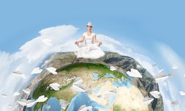Young woman keeping mind conscious. Young woman keeping eyes closed and looking concentrated while meditating on clouds in the air with panoramic view of Earth Royalty Free Stock Images