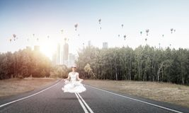 Young woman keeping mind conscious. Young woman keeping eyes closed and looking concentrated while meditating on cloud above the road with beautiful and Royalty Free Stock Photos