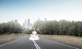 Young woman keeping mind conscious. Young woman keeping eyes closed and looking concentrated while meditating on cloud above the road with beautiful and Royalty Free Stock Image