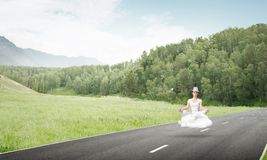 Young woman keeping mind conscious. Young woman keeping eyes closed and looking concentrated while meditating on cloud above the road with beautiful and Stock Photo