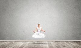 Young woman keeping mind conscious. Young woman keeping eyes closed and looking concentrated while meditating on cloud in the air with gray concrete wall on Royalty Free Stock Image