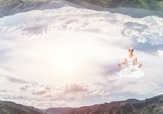 Young woman keeping mind conscious. Young woman keeping eyes closed and looking concentrated while meditating on cloud in the air between two nature worlds Royalty Free Stock Photography
