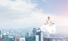 Young woman keeping mind conscious. Woman in white clothing keeping eyes closed and looking concentrated while meditating on cloud in the air with cityscape Stock Image