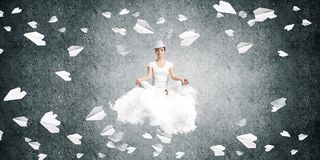 Young woman keeping mind conscious. Woman in white clothing keeping eyes closed and looking concentrated while meditating on flying cloud among flying paper Royalty Free Stock Photos