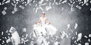 Young woman keeping mind conscious. Woman in white clothing keeping eyes closed and looking concentrated while meditating on flying cloud among flying papers Stock Photo