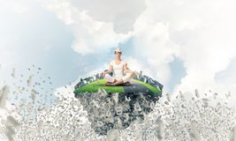 Young woman keeping mind conscious. Woman in white clothing keeping eyes closed and looking concentrated while meditating on island in the air among flying Royalty Free Stock Photography