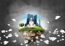 Young woman keeping mind conscious. Woman in white clothing keeping eyes closed and looking concentrated while meditating on island in the air among flying Stock Images