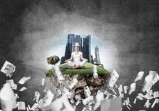 Young woman keeping mind conscious. Woman in white clothing keeping eyes closed and looking concentrated while meditating on island in the air among flying Stock Image