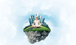 Young woman keeping mind conscious. Woman in white clothing keeping eyes closed and looking concentrated while meditating on island in the air with cloudy Stock Photos