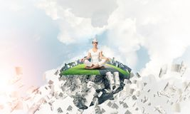 Young woman keeping mind conscious. Woman in white clothing keeping eyes closed and looking concentrated while meditating on island in the air among flying Stock Photos