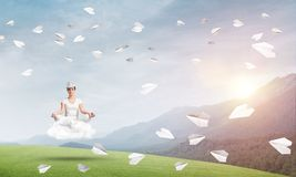 Young woman keeping mind conscious. Young woman keeping eyes closed and looking concentrated while meditating on cloud among flying paper planes with beautiful Stock Photos