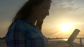 Young woman keeps a control panel of a flying drone at sunset. An exciting view of a young woman who keeps a control panel of a flying drone on the Black sea stock video footage
