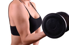 Young woman keeps the dumbbell arm. A young woman holds a black dumbbell hand. side view. arm muscles, chest and dumbbell close up. isolated on a white Royalty Free Stock Image