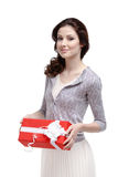 Young woman keeps a gift. Wrapped in red paper, isolated on white Royalty Free Stock Photography