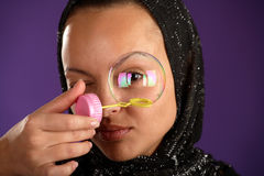 Young woman in kerchief looking through bubble Royalty Free Stock Image