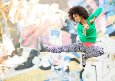 Young woman kicking in mid air. Attractive African American woman outdoors Royalty Free Stock Image