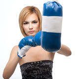 A young woman kicking a punching bag Royalty Free Stock Photography
