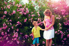Young woman and kid talking in front of blooming garden Royalty Free Stock Photo