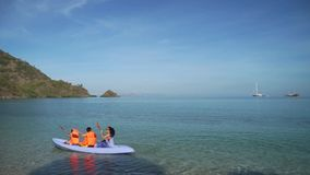 Woman and kids canoeing on beach. Young woman and kids enjoying holiday by canoeing on beach in Labuan Bajo at Flores Island close to Bali, Indonesia stock footage