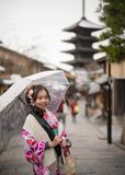 Young woman in kimono clear umbrella. Young woman in kimono holding umbrella front of yasaka pagoda Stock Image