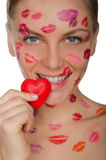 Young woman with kisses on face holding heart in mouth Stock Photos