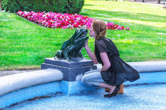 Young woman kisses frog sculpture. Royalty Free Stock Photography