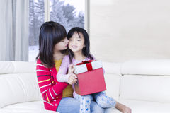 Young woman kisses her child with gift Stock Image