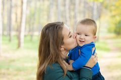 Young woman kisses her little son royalty free stock photo