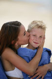 Young woman kissing boy. Portrait of a young mother kissing her son at the beach royalty free stock photo