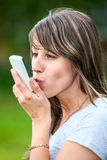 Young woman kissing cellphone Stock Image