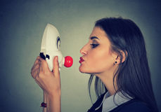 Young woman kissing clown mask. Woman kissing clown mask on gray wall background Stock Images