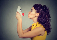 Young woman kissing clown mask. Woman kissing clown mask  on gray wall background Stock Photos