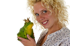 Young woman kissing a frog prince Royalty Free Stock Images