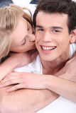 Young woman kissing her boyfriend. Young women kissing her boyfriend on the cheek Stock Images