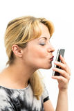 Young woman kissing her mobile phone Royalty Free Stock Image